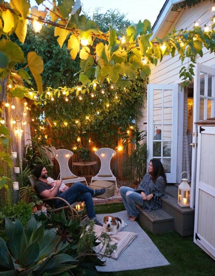 aménager un petit jardin avec des chaises blanches des bougies t des girlandes d ampoules lumineuses