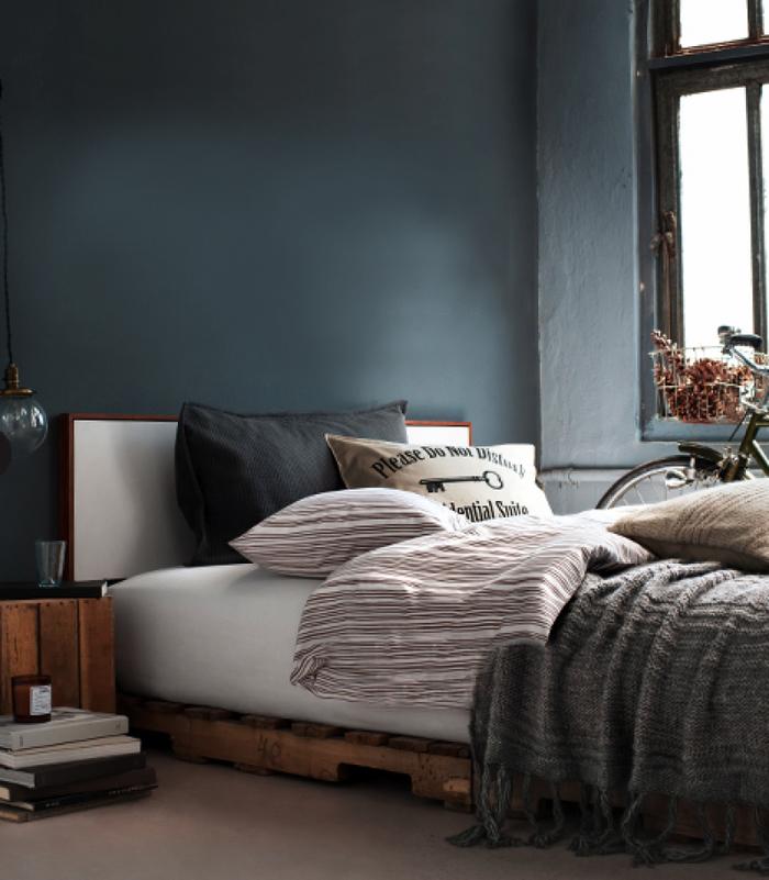 une chambre à coucher bleu canard masculine d'esprit vintage avec un lit palette à ras du sol et une table de chevet en bois récup