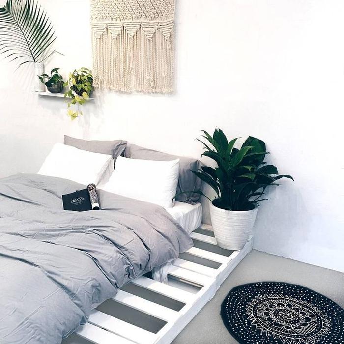 une chambre à coucher blanc et gris d'ambiance bohème chic avec un simple lit palette à sommier dépassant le matelas