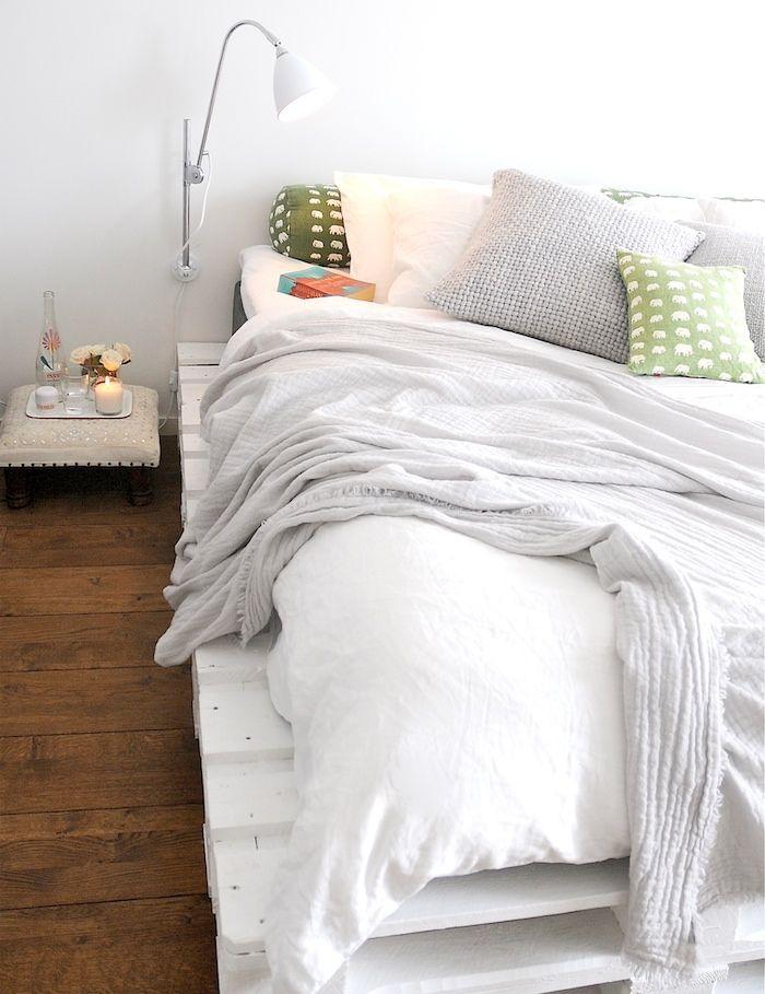 une chambre à coucher ensoleillée à déco minimaliste, avec un lit palette bois peint en blanc qui contraste avec le parquet