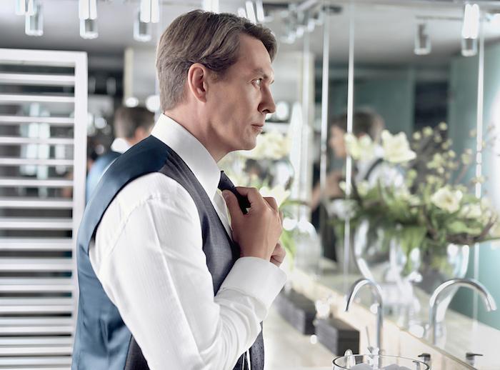 style homme, look professionnel avec chemise et gilet, nouer sa cravate devant le miroir
