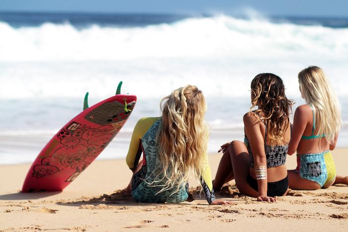 balayage sur cheveux chatain, amies sur la plage, planche de surf en rouge avec dessins noirs, maillots de bains deux pièces en jaune et bleu