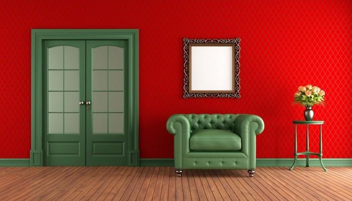 rouge couleur complémentaire vert, canapé et porte verte, revêtement mur rouge, miroir vintage, parquet en bois clair