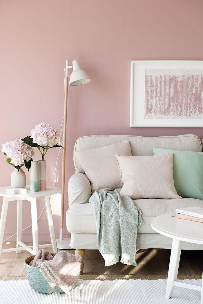 aménagement de salon aux murs pastel, table ronde et blanche avec vase beige et fleurs rose