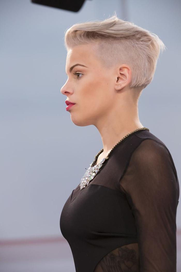 une coupe garçon au côté rasé avec une mèche sculpté et une coloration blond platine