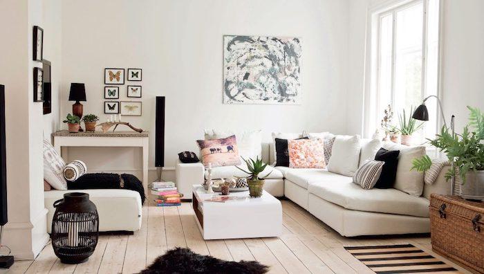 coussins cocooning, plusieurs coussins blanc, noir et rose sur un canapé blanc, parquet clair, fauteuil blanc, table basse blanche, deco murale cadres avec dessins de papillons