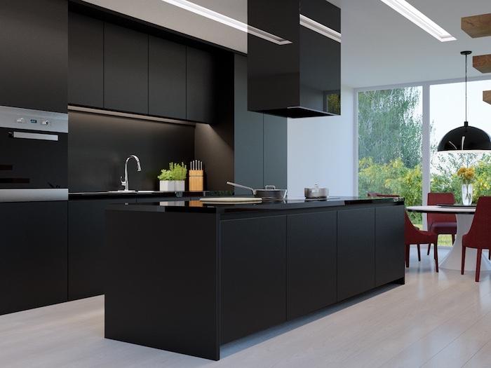 meuble cuisine, table à manger ronde et noir avec chaises rouges, meubles de cuisines noirs sans poignées