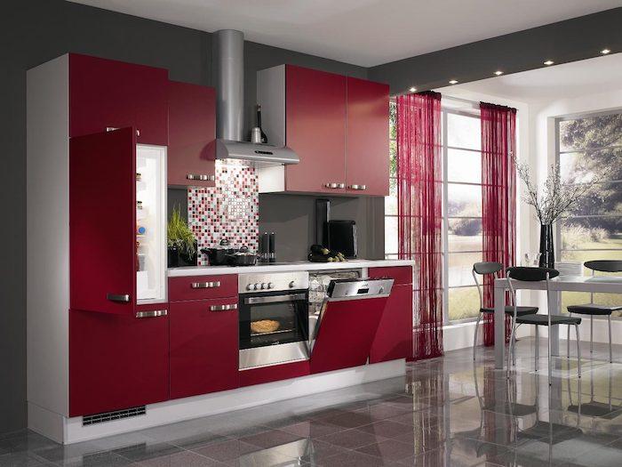 cuisine couleur framboise, façade cuisine rouge, avec plan de travail et aspirateur inox, carrelage gris, table blanche et chaises grises