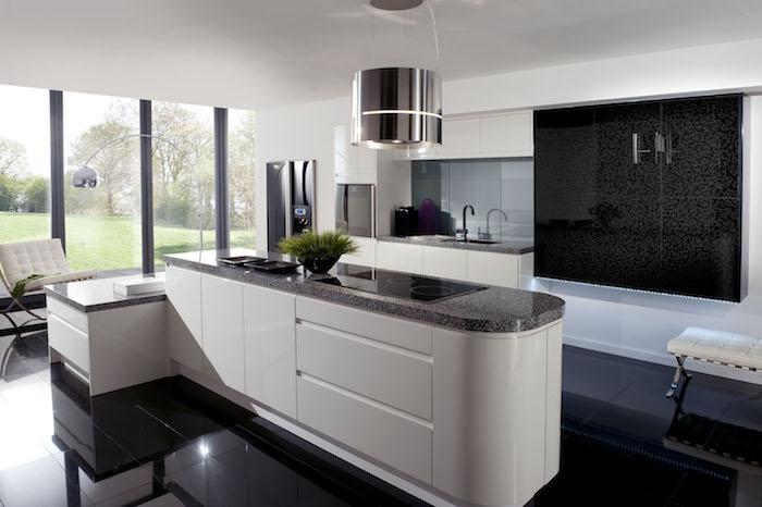petit meuble de cuisine, lampe sur pied en métal, ilot central blanc avec comptoir noir et plaques intelligentes