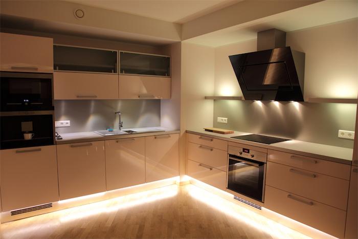 cuisine aménagée, éclairage LED sous les meubles, plafond blanc et sol en bois, évier deux vasques