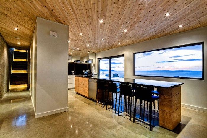 meuble cuisine, ilot central en bois avec comptoir noir, plafond en bois clair, chaises de bar noires