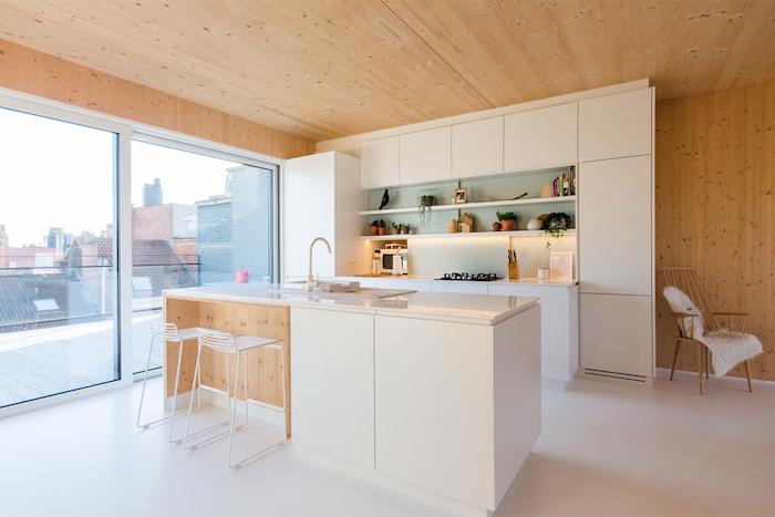 cuisine avec ilot central, porte coulissantes vers le balcon, murs en bois et plancher blanc