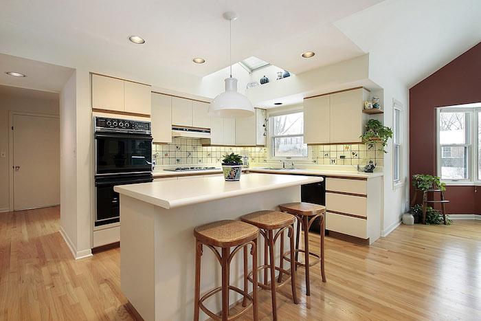 ilot central, plafond blanc avec fenetre, carrelage murs jaunes à motifs floraux, meubles sans poignées