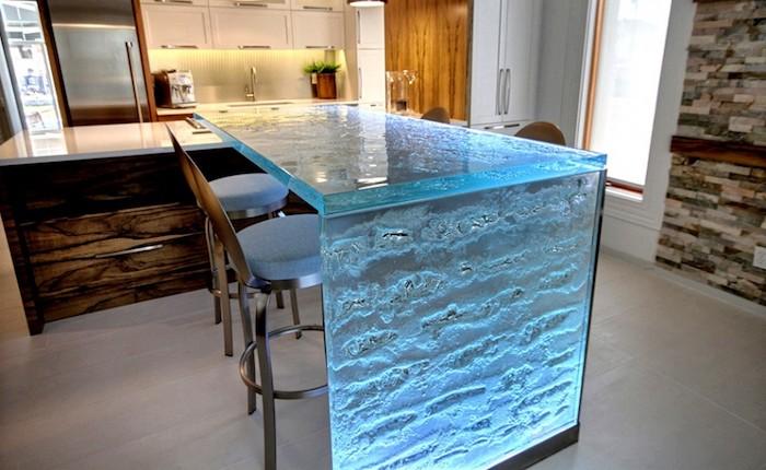 meuble cuisine, mur en pierre, ilot centrale avec comptoir en verre luminaire en bleu, éclairage sous meubles