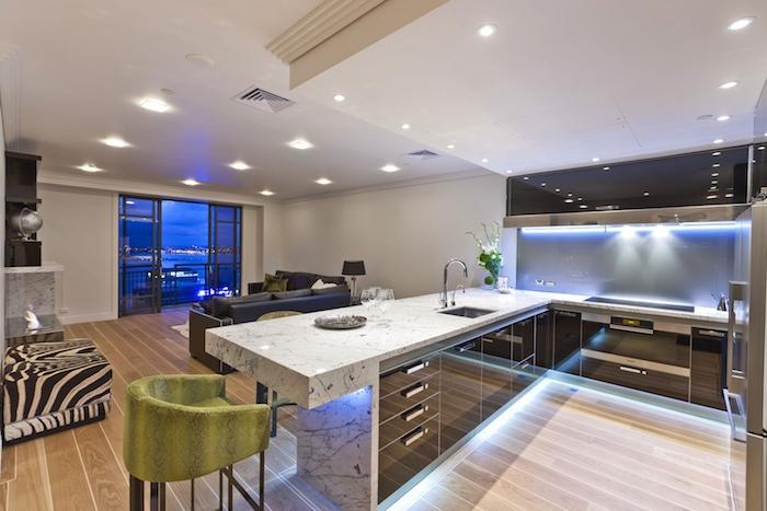 meuble cuisine, revêtement de sol en bois, grand tabouret à motifs zèbre, canapé d'angle en cuir noir