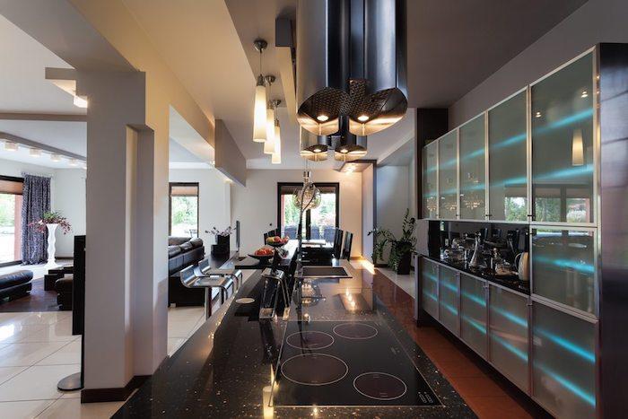 meuble haut cuisine, carrelage de sol en blanc, suspension luminaires en verre, comptoir noir avec plaques