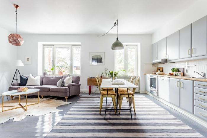 modele de cuisine ouverte sur salon, façade cuisine grise, crédence blanche, salle à manger avec table et chaises, suspension et tapis gris et blanc à rayures, salon canapé gris, table base design, peau animal