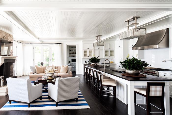 cuisine ouverte sur salon, canapé couleur ecru, table basse bois, fauteuils noir et blanc, parquet marron foncé, tapus blanc et bleu, cuisine campagne chic bois blanc et marron