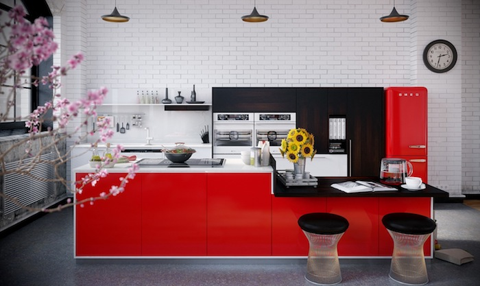 deco rouge et noir, frigo et ilot central rouge, plan de travail noir et blanc, revêtement sol gris, meuble cuisine en bois marron, mur en briques blanches, suspensions industrielles