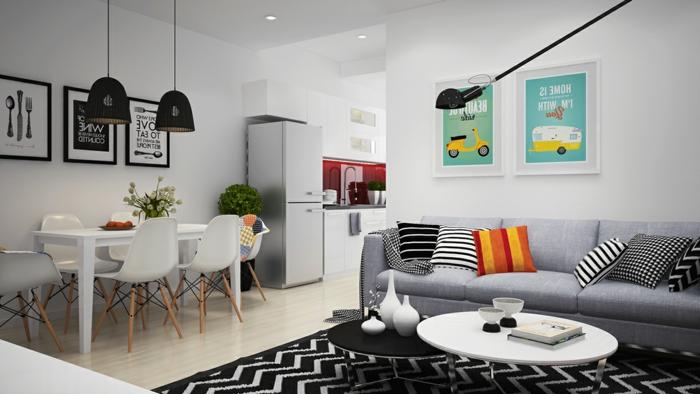 modele de cuisine semi ouvere sur salon, deco scandinave pas cher, mur avec affiches colorés et graphiques, salle à manger avec chaises et table blanche, tapis noir et blanc, canappé gris, tables gigognes noir et blanc