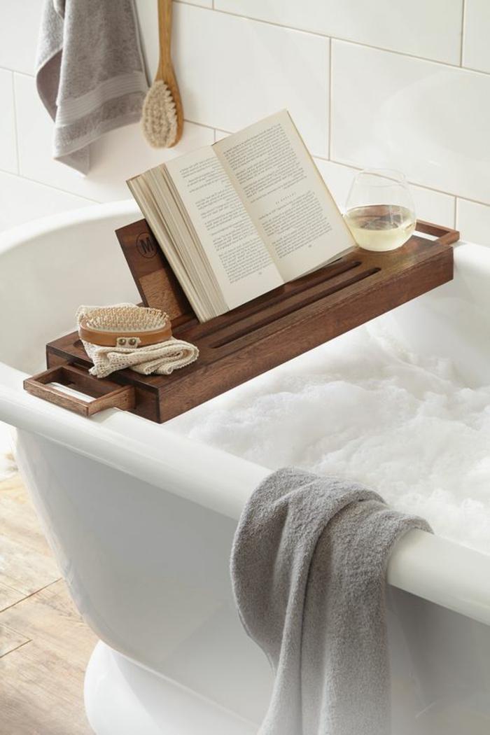 déco salle de bain zen, accessoire en bois sur une baignoire blanche, carrelage mural blanc