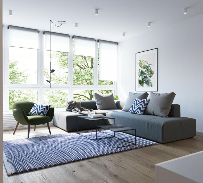 mobilier scandinave, canapé gris et fauteuil vert, tapis blanc et bleu, parquet clair, vue sur un paysage vert