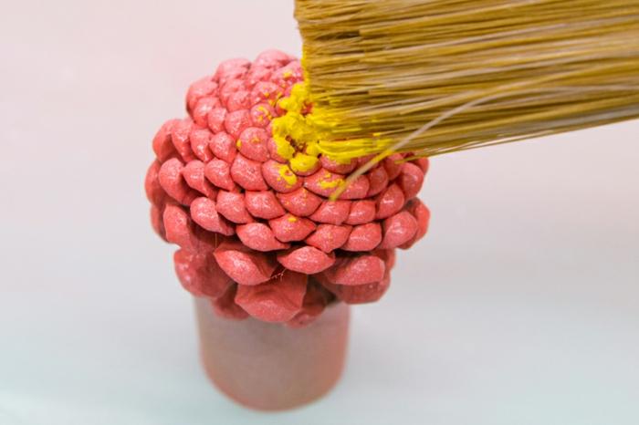 décoration de noel à fabriquer, peindre une pomme de pin rose et jaune
