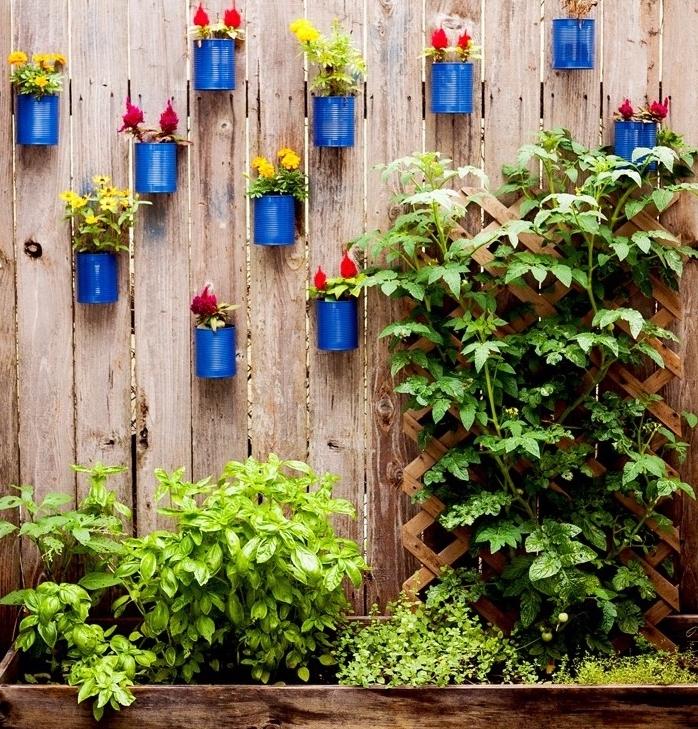 déco a faire soi meme recup, des boîtes de conserve, repeintes en bleu et rangées sur une palissade en bois, deco fait maison exterieur moderne