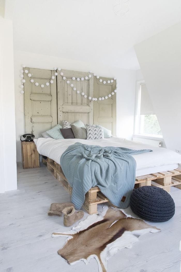 une chambre à coucher accueillante de style scandinave qui adopte la tendance récup avec un lit en palette europe et une têtê de lit en porte ancienne