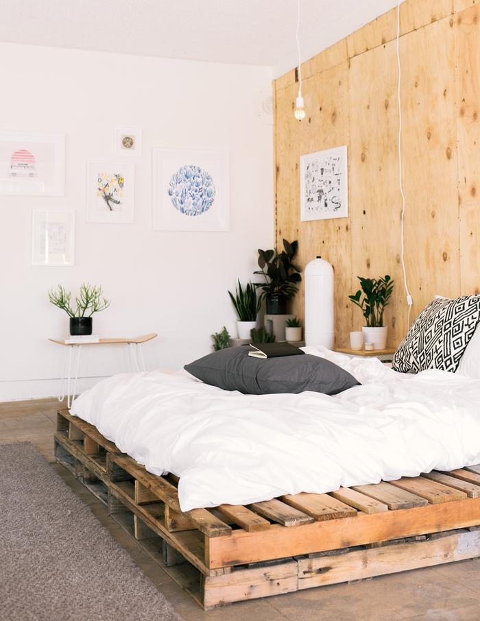 une chambre à coucher en blanc et bois de style bohème chic avec un lit palette et un mur en contreplaqué