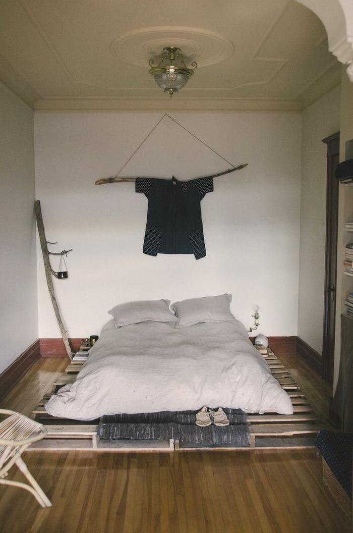 une déco de chambre à coucher récup et minimaliste avec un sommier en palette de bois et des branches de bois détournées en objets déco