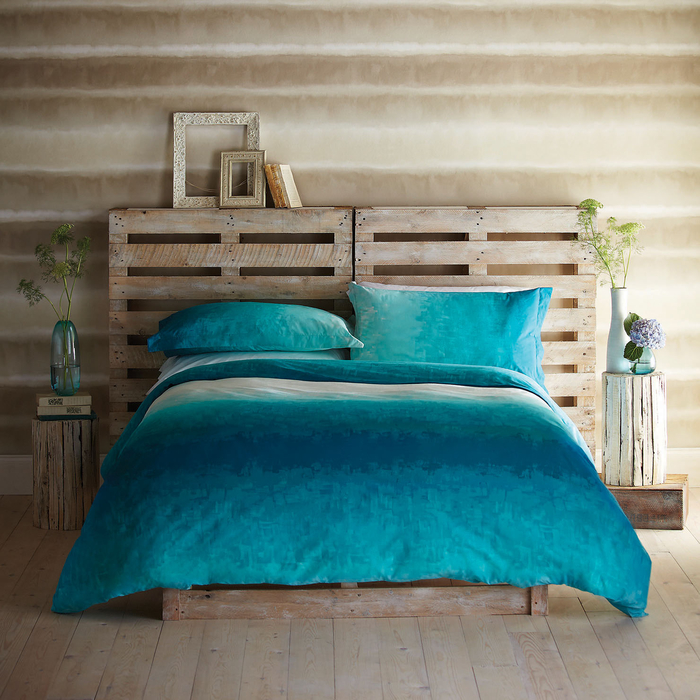 une chambre à coucher avec déco de style bord de mer en beige et turquoise, lit en palette avec des tables de nuit en rondin de bois