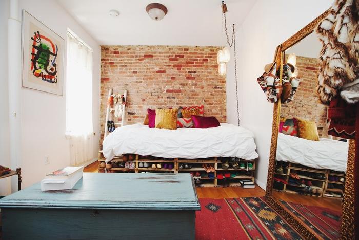 aménagement intelligent d une petite chambre à coucher bohème chic avec un grand miroir adossé au mur et un lit palette avec espace de rangement
