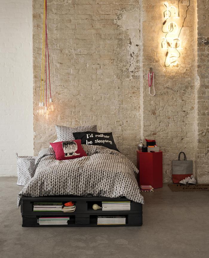 une chambre à coucher en blanc, rouge et noir aménagée dans un style industriel avec un lit palette au centre de l'espace