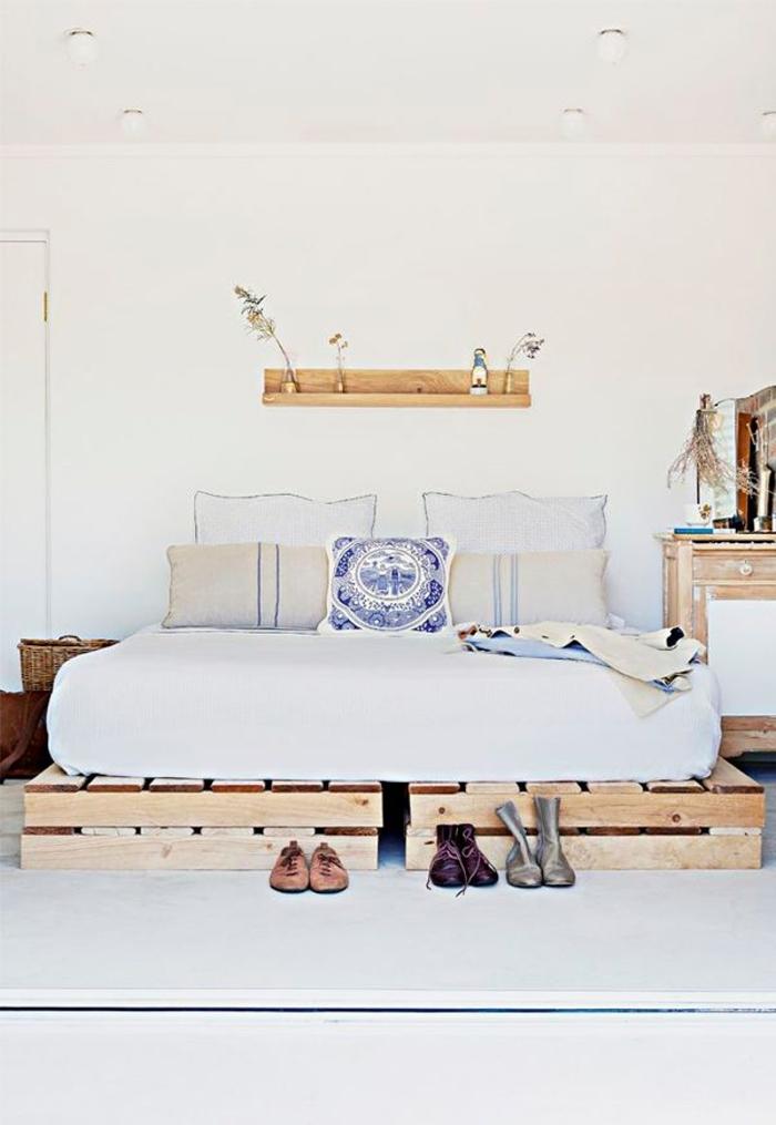 chambre à coucher en blanc et bois de style scandinave et d'esprit minimaliste avec un lit en palette fonctionnel et gain-d'espace