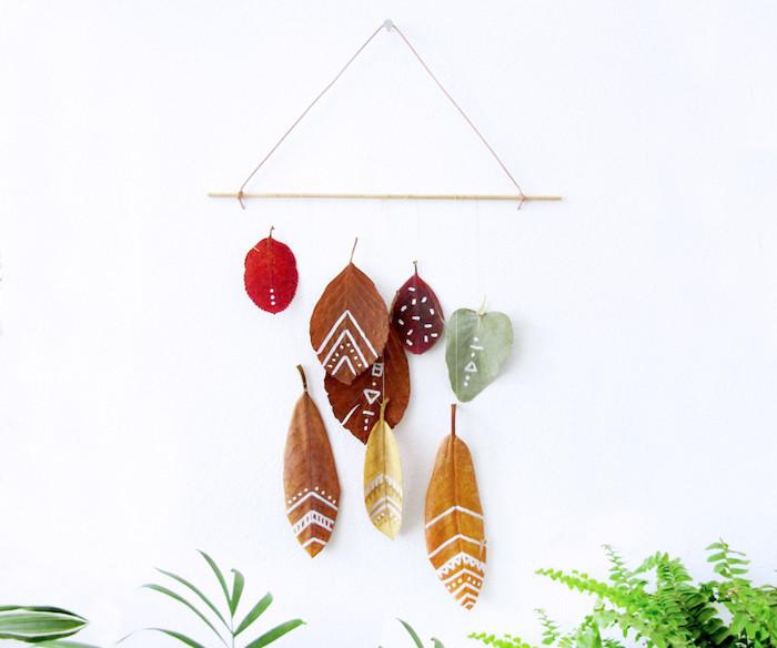 une decoraion automnale de feuilles mortes suspendues à une brindille en bois, feuilles mortes décorées aux motifs au feutre blanc, bricolage facile