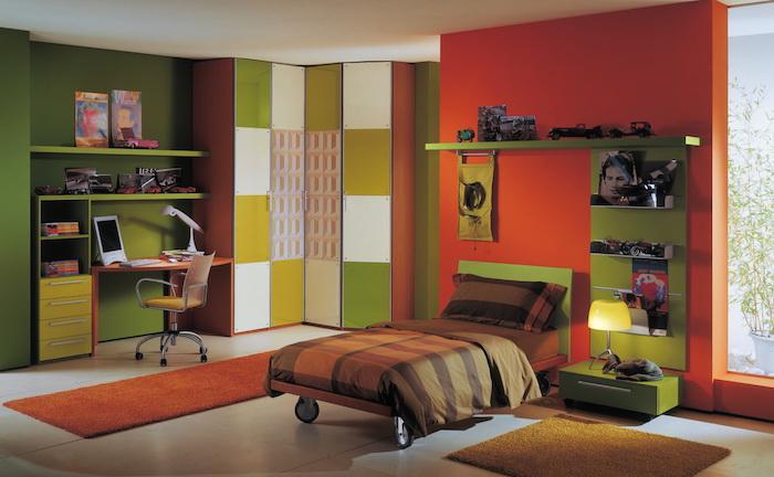 couleur complémentaire du rouge, mur d accent rouge tirant vers l orange, petit lit à roulettes, étagère verte, coin bureau mur vert, chaise enfant, amenagement chambre enfant