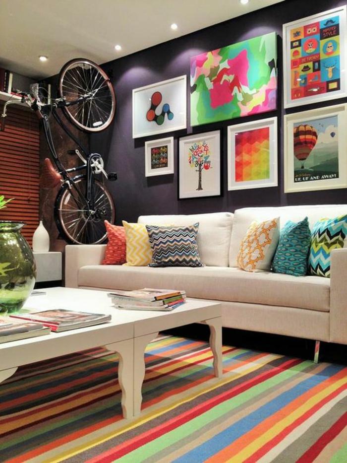 chambre ado lit ado avec vélo a cote du canapé avec des tableaux très colorés
