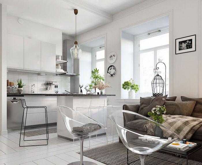cuisine ouverte sur salon cocooning avec canapé et coussins gris, tapis noir et blanc, fauteuils transparentes, façade cuisine blanche