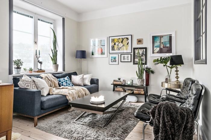 tapis cocooning gris dans un salon nordique, canapé bleu marine, table basse moderne, chaises en metal et cuir, deco murale avec pièces d art, coussins decoratifs