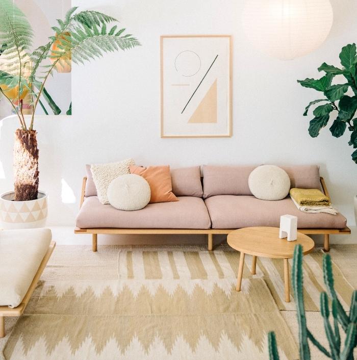 idee deco cocooning, canapé et table en bois, coussins d assise rose, tapis beige, plusieurs plantes exotiques vertes, suspension boule