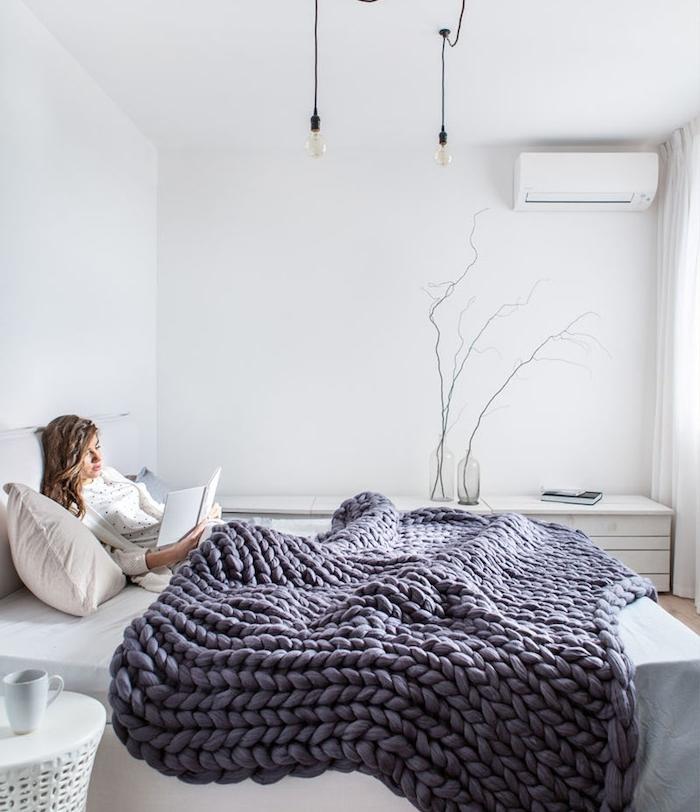 idée déco chambre cocooning, avec linge de lit blanc, couverture en laine à grosse mailles pour une ambiance chaleureuse, table de nuit blanche