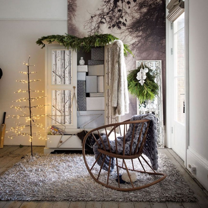 tapis cocooning dans une habitation hygge, chaise à bascule en bois, plaid gris à grosses mailles, armoire blanche, arbre noel avec guirlande lumineuse, panneau decoratif motif foret nordique
