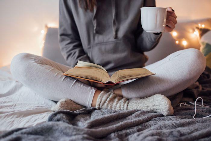 exemple deco cocooning, de type hygge, linge de lit blanc et gris, guirlande lumineuse, livre et tassé de café