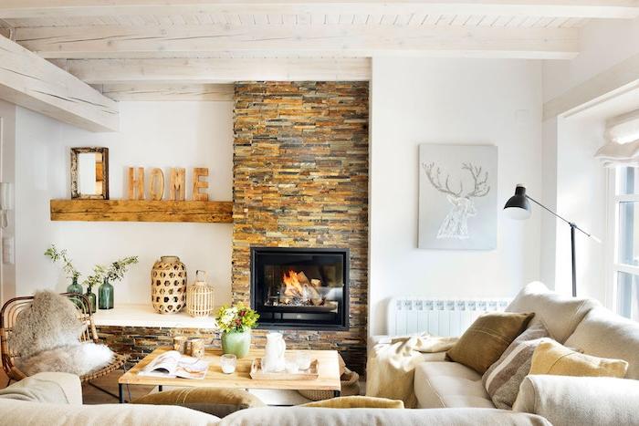 deco cocooning dans un salon, cheminée en pierre, canapés blanc cassé, coussins blanc, marron et gris, table basse en bois et metal, chaise tressée