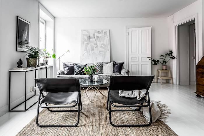 deco cocooning, canapé gris tapis beige chaises noires en cuir, murs blancs, parquet blanchi, table basse design, couverture grise enveloppante
