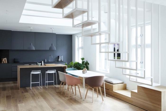 idée de façade cuisine et ilot cuisine gris anthracite, parquet clair, table blanche, chaises pastel, escalier blanc