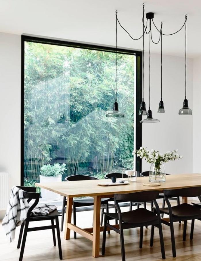 deco scandinave salle à manger avec table bois massif, chaises noires, suspensions industrielles, grande fenêtre