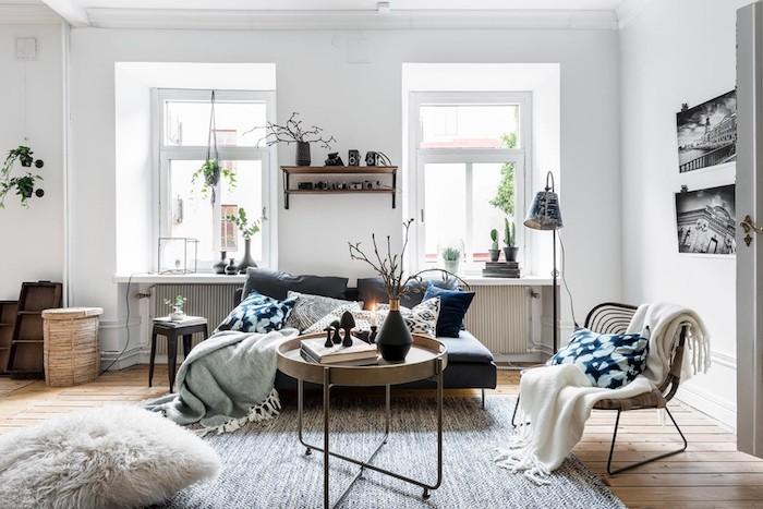 idee deco cocooning avec canapé gris, chaise et table design scandinave couverture enveloppante, pouf avec taie de fausse fourrure, murs blancs, coussins gris, blanc bleu