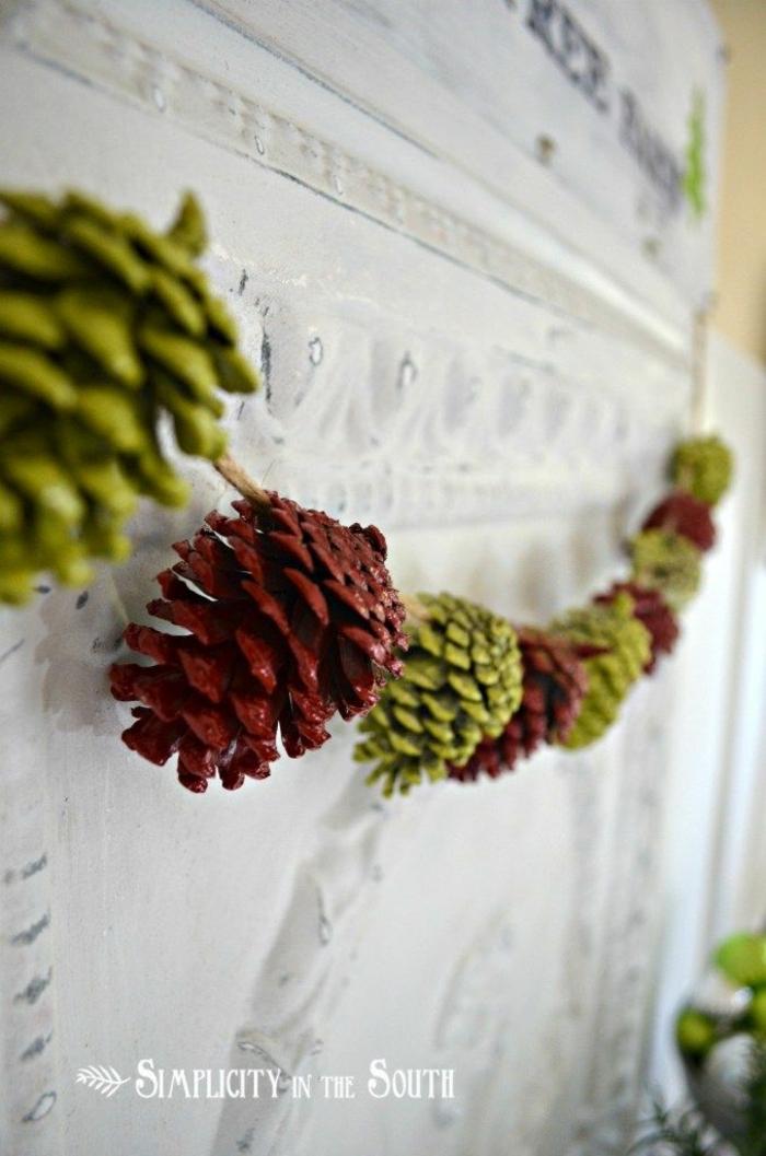 deco noel a fabriquer, guirlande de pommes de pin colorées et accrochées au mur